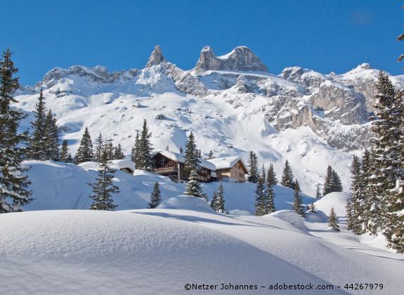 Zwei Häuser in verschneiten Bergen